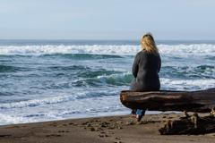 Woman sitting on a driftwood log - stock photo