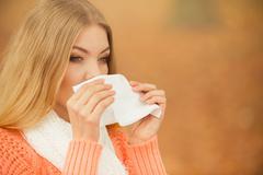 Sick ill woman in autumn park sneezing in tissue. Stock Photos