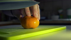 Man cutting a tangerine in his kitchen 4k Stock Footage