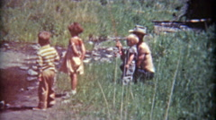 1961: Dad letting kids hold fishing pole on banks of the grassy river. - stock footage