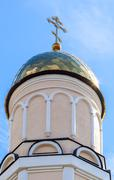 Golden dome of Russian orthodox church with cross against blue sky Stock Photos
