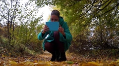 The girl sits down and takes a picture in the park. She used blue tablet. Stock Footage
