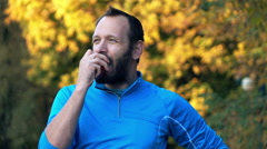 Happy jogger eating apple in autumn park, super slow motion Stock Footage