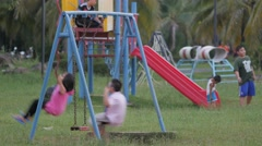 Thai boy and girl on swing in playground,Ubon Ratchathani,Thailand Stock Footage