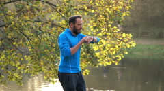 Man jogging in autumn park checking pulse on smartwach, super slow motion Stock Footage