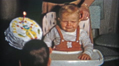 1961: Big 1st birthday cake for boy wearing suspenders in high chair. Stock Footage