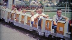 1961: Children on mini train circling at local amusement park. Stock Footage