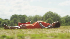 4K Happy pregnant woman relaxing in the park with hands on her belly - stock footage