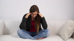 Woman sad stressed sitting on couch at home 4K - stock footage