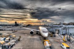 Sunset Over Commercial Aircrafts on Airport Tarmac Stock Photos