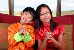 Two Kids Offering Chinese New Year Greetings - stock photo