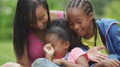 4K Portrait of happy African American mother & children having fun in the park Stock Footage