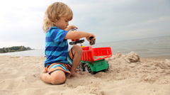 Cute child loads sand with the help of toy excavator in the truck Stock Footage