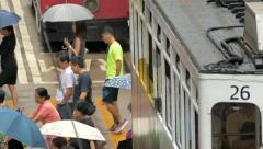 Traffic in Hong Kong with double decker tram and people carrying umbrellas in th Stock Footage