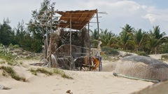 Old fishing boat and fishing lodge on the sand beach. Vietnamese lifestyle Stock Footage