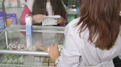 Pharmacist giving health advice to the buyer in pharmacy Stock Footage