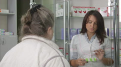 Medicines counter assistant giving advice to senior customer at pharmacy Stock Footage