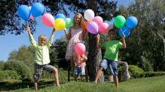 Happy family with colorful balloons in green park. - stock footage