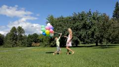 Boy giving balloons to his mother in spring park. Stock Footage
