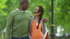 4K Happy mixed ethnicity couple expecting a baby, taking a walk in the park - stock footage