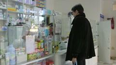 Team of pharmacists advising customer in pharmacy drugstore Stock Footage
