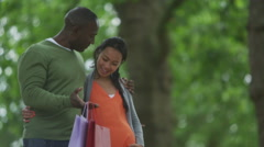 4K Happy mixed ethnicity couple expecting a baby, walking in park with shopping  - stock footage
