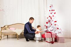 Little girl play with her dad  near Christmas tree Stock Photos