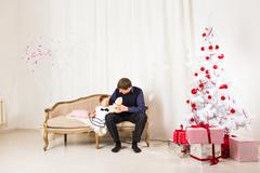 Little girl play with her dad  near Christmas tree - stock photo