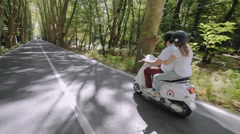 Rear side view of young Caucasian couple riding their scooter Stock Footage