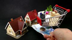 Full model shopping trolley pushed alongside two model houses, then euros added. Stock Footage