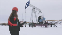 Female engineer and oil man working together in an oilfield, teamwork - stock footage