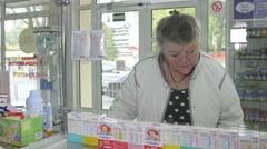 Pharmacist advising senior customer at russian pharmacy drugstore Stock Footage