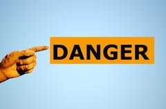 finger with rectangular orange label DANGER - stock photo