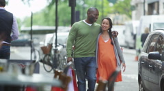 4K Happy couple expecting a baby walking with shopping bags in the city Stock Footage