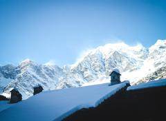 Snow-covered roof on a background of mountains - stock photo