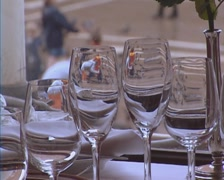 gleaming wine glasses on windowsill with the reflection from city square - stock footage