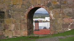 People walking up to an archway in wall at Varberg Fortress Stock Footage