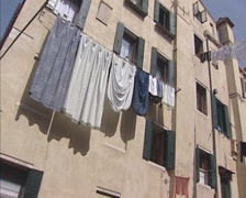 Venice row houses, narrow passage + laundry lines spanning the canal Stock Footage