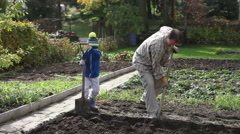 Father and son, digging and shoveling in the garden autumn time Stock Footage