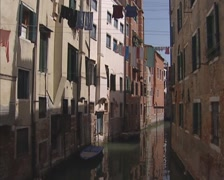 Narrow canal in Venice +  tilt up row houses + laundry lines Stock Footage