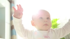 Baby sitting in sunny living room on the ground Stock Footage