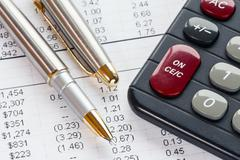 Accounting in process with calculator and pen - stock photo