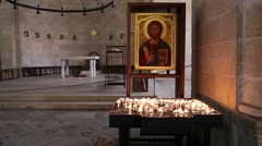 Many candles in front of Jesus portrait at Church of the Multiplication, Israel - stock footage