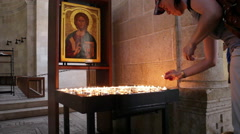 Woman pilgrim lights candle at the Church of the Multiplication, jesus, Israel - stock footage