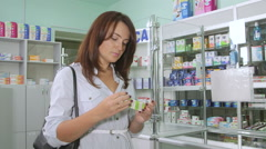 Female customer reading OTC medicine drug facts label at russian pharmacy Stock Footage