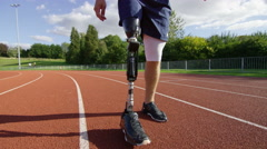 4K Disabled athlete with prosthetic leg warms up before a run at running track - stock footage