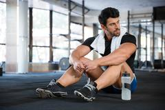 Athlet sitting on the floor in gym - stock photo