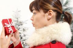 Woman with Christmas gift, amazed Stock Photos