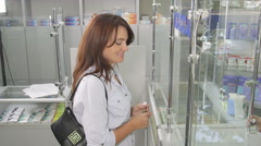 Female customer reading OTC medicine drug facts label at pharmacy Stock Footage