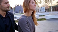 Couple arguing on a bench. Girl is mad at her boyfriend. Outdoor photo. - stock footage